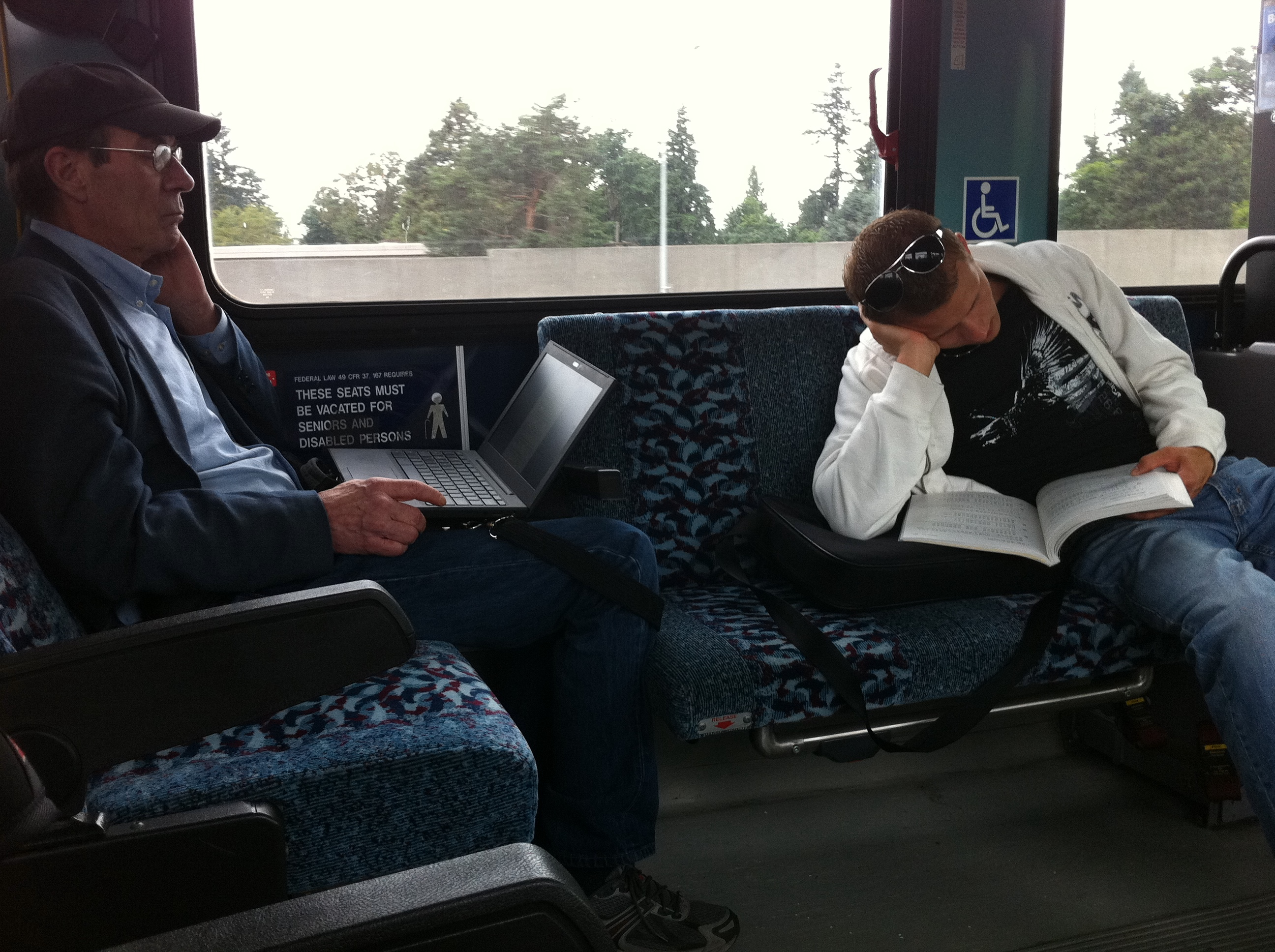 two men reading on the bus